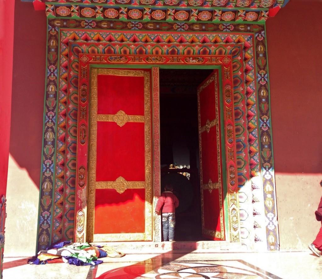 Child peering through the main door of the Surmang Shedra